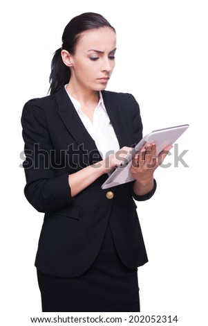 Working on digital tablet. Confident young woman in formalwear working on digital tablet and smiling while standing isolated on white - stock photo