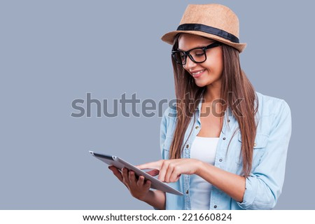 Working on her new tablet. Beautiful young girl working on digital tablet  while standing against grey background - stock photo