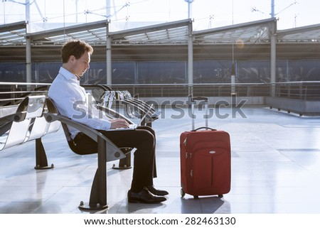 Working on laptop in airport while waiting for flight - stock photo