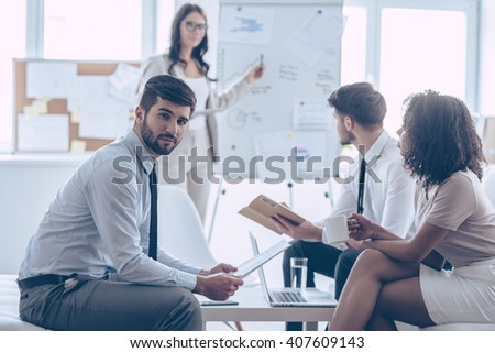 Working on new business strategy. Handsome young man holding documents and looking at camera while sitting at couch in office with his coworkers