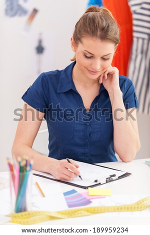 Working on new fashion look. Attractive female fashion designer sketching while sitting at her working place