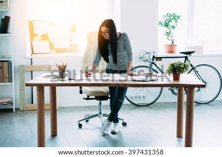 Working on new project. Full length of young beautiful Asian woman making some notes at blueprints while leaning to the table in office - stock photo