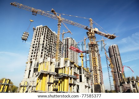 Working on place with many tall buildings under construction and cranes under a blue sky - stock photo