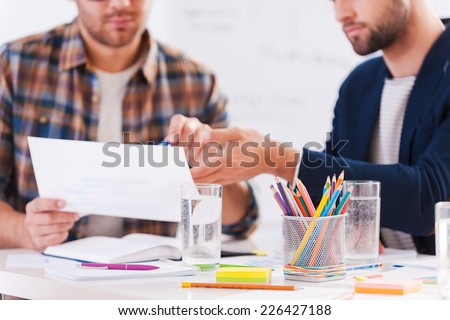 Working on project together. Close-up of two confident business people in smart casual wear sitting together at the table and discussing something - stock photo