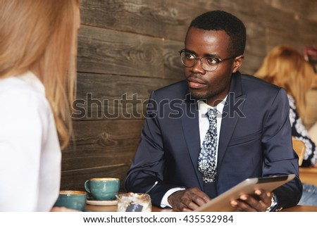 Working on project together. Multiethnic business partners having a conversation at a cafe: African man in glasses holding tablet, listening attentively to his redhead Caucasian female colleague - stock photo