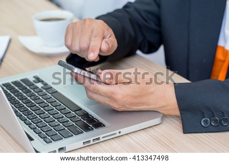 Working on smartphone and laptop, close up of hands of business man