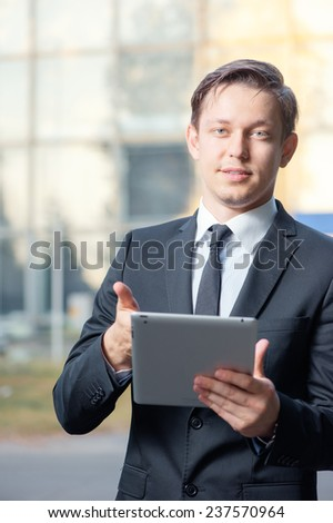 Working on tablet. Cheerful young caucasian businessman in formal wear working on digital tablet and looking at camera while standing outdoors