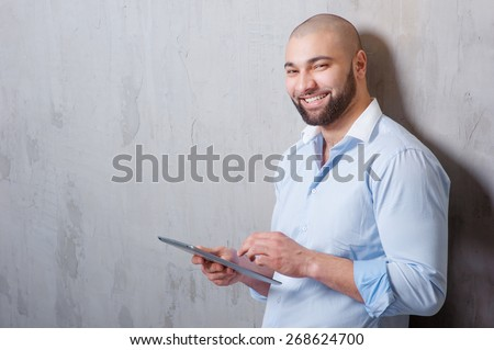 Working on tablet computer. Cheerful young arabic man working on digital tablet and looking at camera while leaning on grey wall. - stock photo