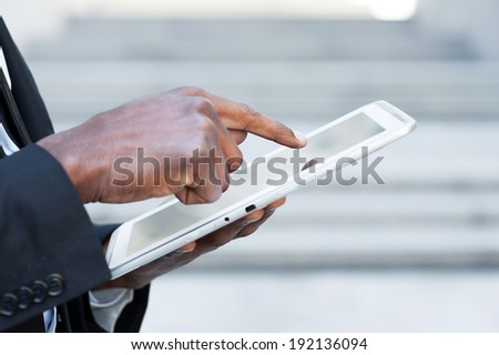 Working on tablet. Side view cropped image of African man in formal wear working on digital tablet while standing outdoors - stock photo