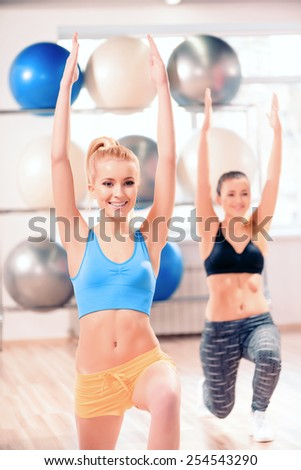 Working on their fitness. Two beautiful young women in sports clothing exercising together and smiling while standing against rows of fit balls in sports club - stock photo
