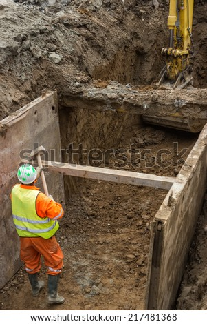 working on trench construction, underground installation by open trench method - stock photo