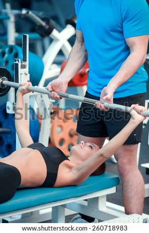 Working out. Concentrated young beautiful woman in sports clothing doing exercises in the gym with a barbell lying on the bench while her sports instructor controlling the workout