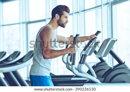 Working out for best body. Side view of young handsome man in sportswear looking away while working out on stepper at gym - stock photo