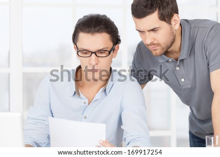 Working out problems. Confident young man sitting at the table and looking at the document while his colleague standing near him - stock photo