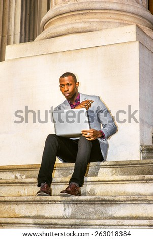 Working outside. Dressing in light gray blazer, black pants, brown leather shoes, a young guy sitting on stairs outside office, hands holding laptop computer, mobile phone, thinking. Instagram effect. - stock photo