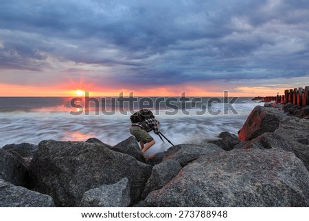 Working photographer on the rocks along the coast of Folly Beach near Charleston, South Carolina at sunrise under a storm cloud-filled sky.