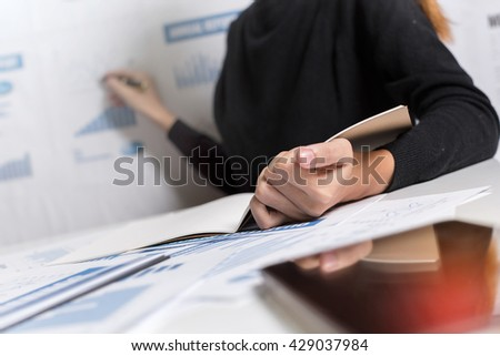 Working place of business woman work with pie chart and financial report on desk and accounting board display.