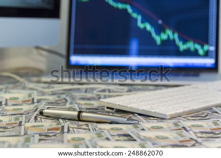 Working place of trader. The table covered by cash notes, keyboard and financial charts on the computer screens - stock photo
