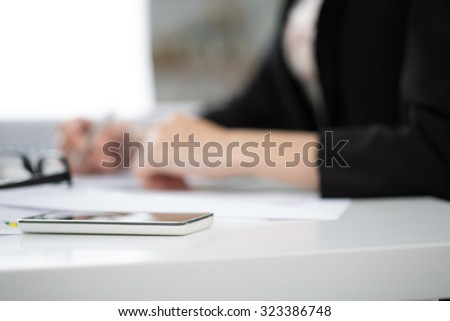 Working place view. Focus on mobile phone with business woman writing something on background. Copyspace - stock photo