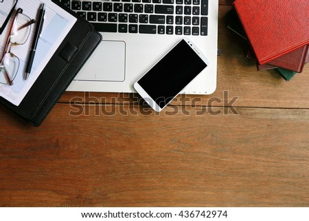 working place with laptop on table,Layout of comfortable working space on wooden, internet laptop headphone phone notepad pen eyeglasses laying on it   - stock photo