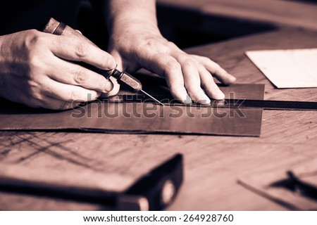 Working process of the leather wallet in the leather workshop. Woman's hands holding crafting tool and iron ruler. Monochrome cream tone. Black and white photography. - stock photo