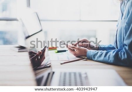 Working process photo. Account manager working wood table with new business project. Typing contemporary smartphone screen. Modern notebook reflections screen.Horizontal.Film effect,blurred