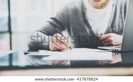 Working process photo. Manager working table with new startup project. Modern notebook table. Using pen for sign contract. Horizontal. Film effect. Blurred background