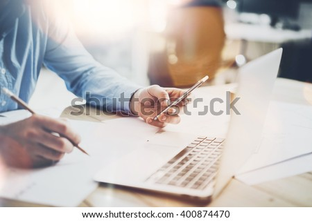 Working process photo. Manager working wood table with new  project. Modern notebook table. Pencil holding hand, typing  contemporary smartphone. Horizontal. Flares, film effect. Blurred background - stock photo