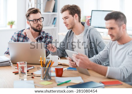 Working process. Three young business people working together while sitting at their working place in office - stock photo