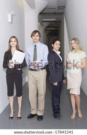 Working professionals standing in corridor - stock photo