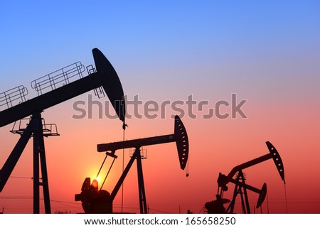 Working pumping unit under the setting sun   - stock photo