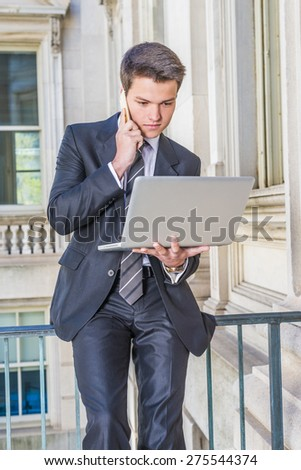 Working remotely. Dressing in black suit, necktie, a young businessman sitting on railing inside vintage style office building, working on laptop computer, talking on mobile phone in the same time.