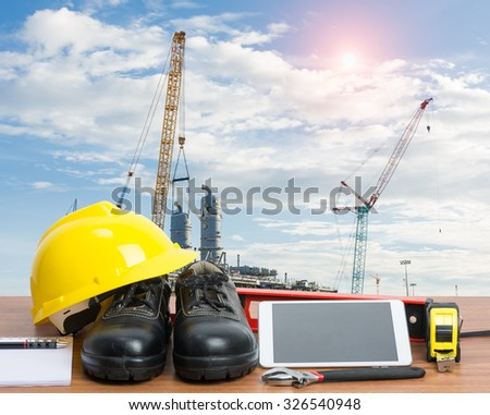Working table engineer with tablet and tools in building construction crane - stock photo