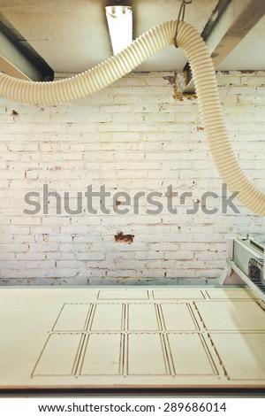 Working table of CNC wood router machine, white painted brick wall with a hole and flexible ventilation duct pipe attached to a ceiling. Router table with etching on deck - stock photo