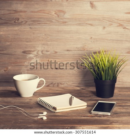 Working table with notepad, coffee cup , pen , smartphone , headphone, plant pot. Wooden table background with copy space on top. Instant photo vintage split toning color effect. - stock photo
