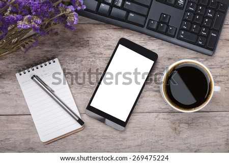 working table with smart phone note paper pen flowers and cup of - stock photo