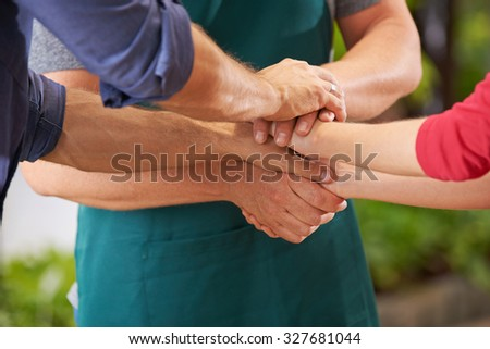 Working team stacking many hands for motivation - stock photo
