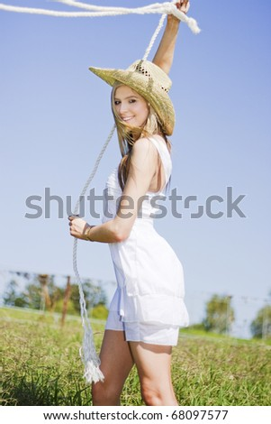 Working The Land A Lassoing Lady Smiles In A Sexy Portrait Of The Outback Lifestyle - stock photo