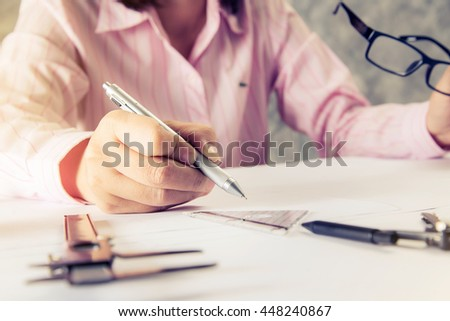 Working time.Architect sketching construction project on wooden table