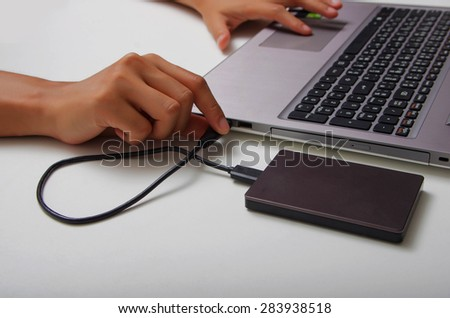 Working time, external harddisk connect by USB port to laptop computer - stock photo