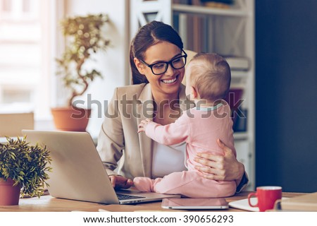 Working together is so fun! Cheerful young beautiful businesswoman looking at her baby girl with smile while sitting at her working place