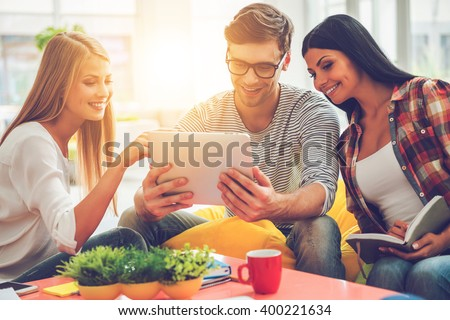 Working together. Three happy young people looking at digital tablet and smiling while sitting on the colorful bean bags in office - stock photo