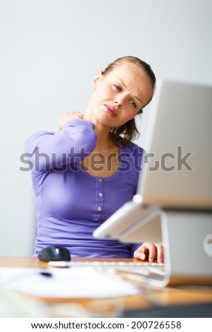 Working too hard - young woman working on a computer at an office, having sore back, being overloaded with work, sitting too much, putting too much stress on her eyes,.. - stock photo