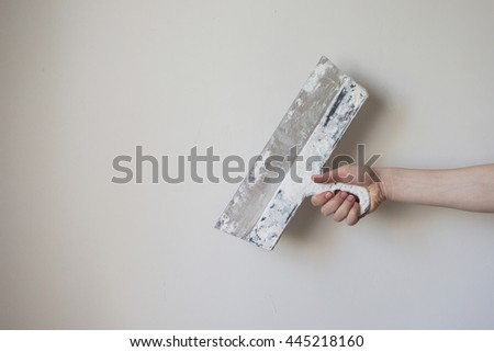 Working tool, spatula in hand on a light background, work plasterer, painter, to make repairs.Trowel in man's hand on a background of a white wall . Space for text - stock photo