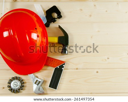 Working tools. A helmet, a hammer, an adjustable spanner and other tool on a wooden background. - stock photo