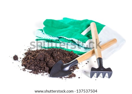 Working tools and a handful of earth on a white background