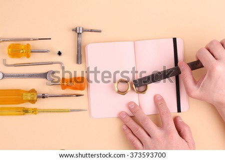 Working tools background with man hands on notebook making notes.  - stock photo