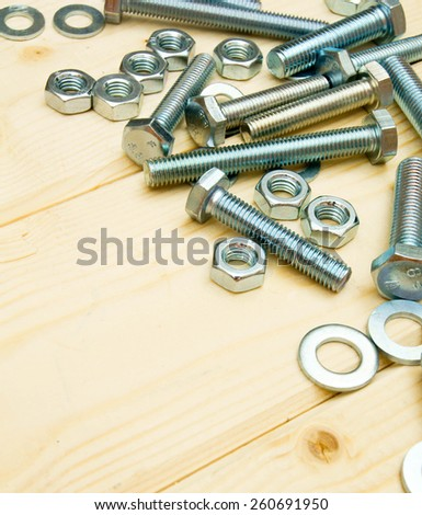 Working tools. Fixing elements (nuts, screws) on wooden background.
