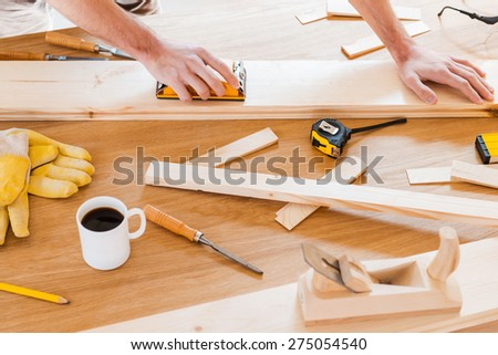 Working tools for carpenter. Close-up of male carpenter working at the wooden table with diverse working tools laying on it  - stock photo