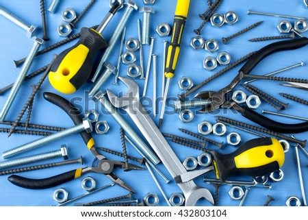working tools near the bolts to screws and nails and screws scattered on a blue background - stock photo